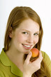 Portrait of a young woman eating an apricot and smiling