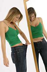 Side profile of a young woman looking at her waist in front of a mirror