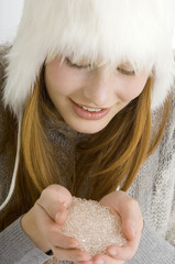 Close-up of a young woman holding crystal salt in her cupped hands and smiling