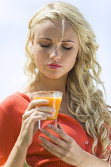 Portrait of a young  blond woman holding a fruit juice glass