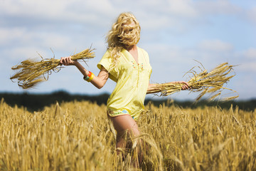 Young woman holding wheat in a field