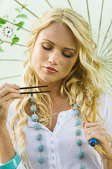 Young woman holding chopsticks and umbrella