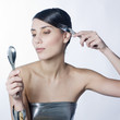 woman combing her hair with a silver fork