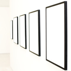 Five empty frames on white wall exhibition
