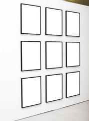 Nine empty frames on white wall exhibition