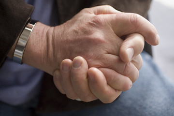 Man's hands clasped.