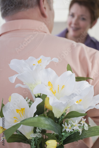 Mature man hiding flowers from a woman.