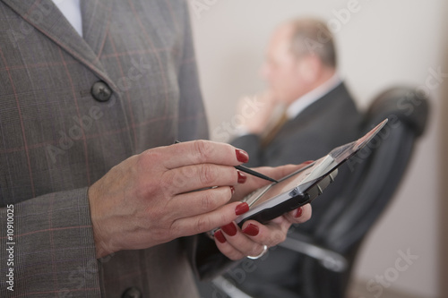 Business woman using PDA and man sitting.