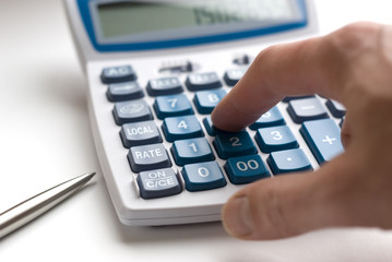 Hand typing on financial calculator