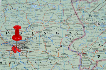 Pin pointing Warsaw on polish map in atlas