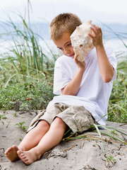 Boy listening to seashell at beach