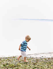Boy walking near ocean at beach