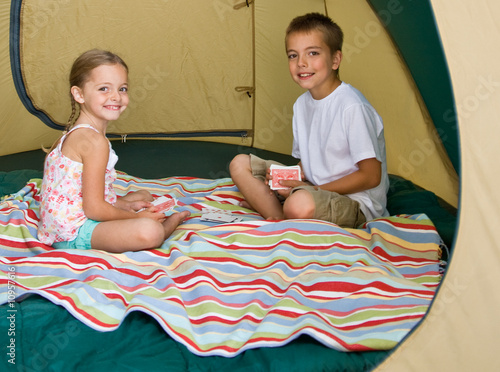 Brother and sister playing cards in tent