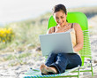 Woman using laptop at beach