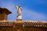 Stone statue of Jesus on a tile roof in Granada