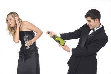 man opening a champagne bottle at a party with her girlfriend