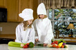 two young cooks cutting vegetables