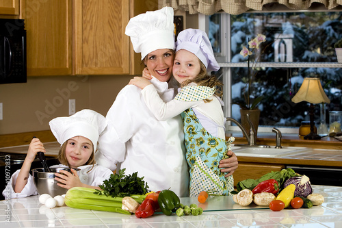 Happy family cooking dinner in chef uniform