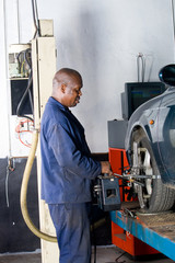 african mechanic working on a vehicle wheel alignment