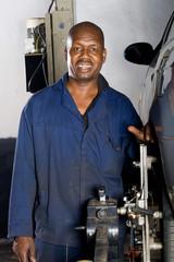 african mechanic working on vehicle wheel alignment