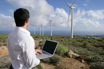 Homme avec ordinateur portable sur un site d'éoliennes