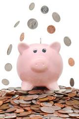 Coins falling over a piggy bank