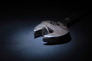 Rusty spanner with coin lying on dark background