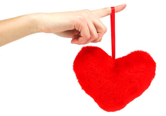 Red wooden heart hanging down from female hand