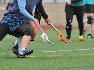 lacrosse players going for the ball.