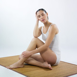 relaxed woman sitting on a bamboo mat poster