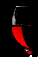 half of red wine glass isolated on black background