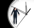 Businessman hangs on an arrow of clock