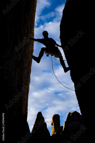 Climber clinging to a steep rock.