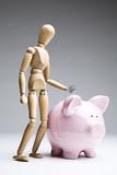 Manikin dropping a coin into a piggy bank poster