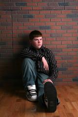 teenage boy sitting on floor