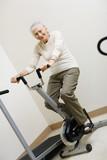 Senior woman pedaling on stationery bike poster