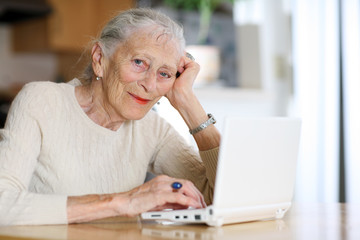 Elderly woman typing with computer at home