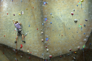 Young man climbing on a climbing wall.