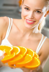 Young happy woman with plate of orange. Focus on woman