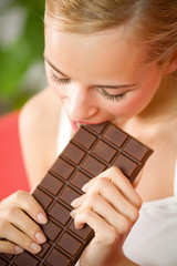 Young beautiful woman eating chocolate at home