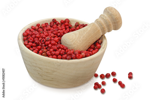 Dried pink pepper berries in mortar isolated on white