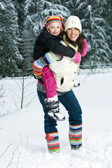 Mom giving daughter piggyback ride in the snow
