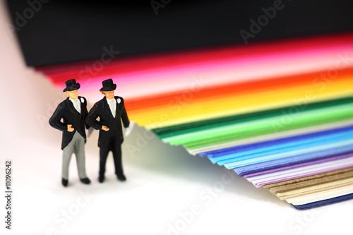 Gay men standing by rainbow paper. Gay marriage concept.
