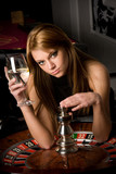 Beautiful woman in casino, holding a glass of some beverage poster