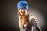 Agressive young beautiful sporty girl in blue winter cap poster