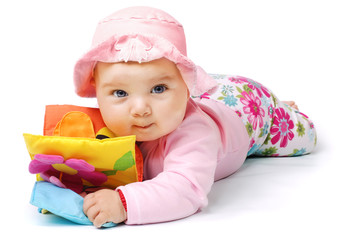 Laying baby in pink clothes with toy