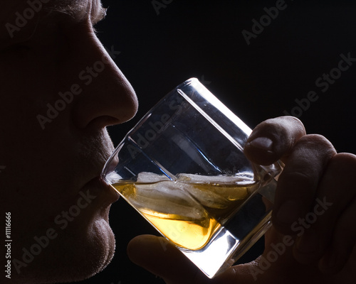 The man drinks whisky with ice