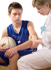 a teams doctor giving first aid the young sportsman