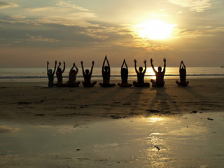 Yoga class at sunset by the ocean