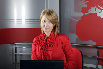 beautiful smiling TV Presenter in front of the laptop on the air